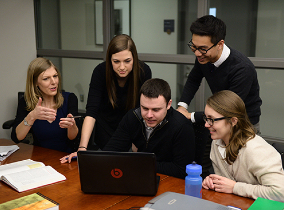 5 students convene around a laptop during class