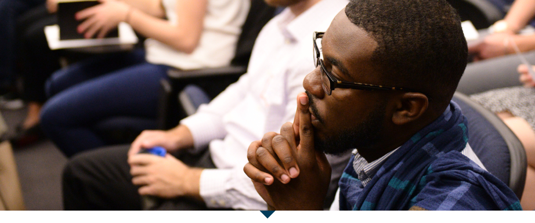African American male student listens attentively during orientation.
